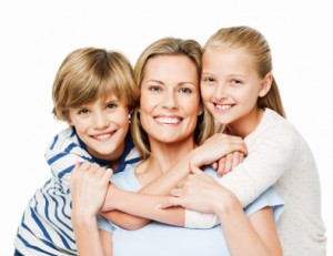 Two children embrace their mother as they smile for the camera. Horizontal shot. Isolated on white.